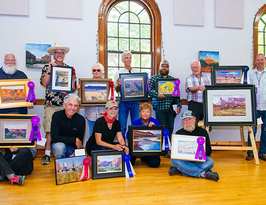 Group of artist posing showing there paintings for a picture