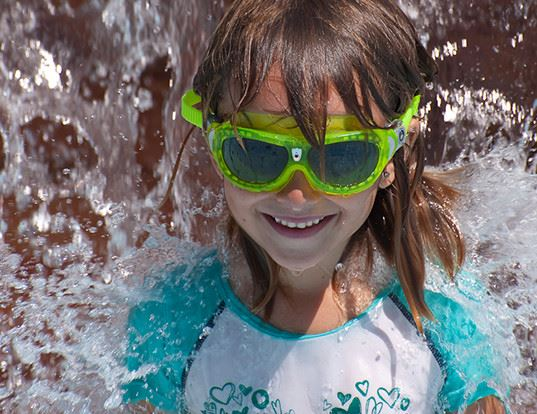 smiling girl having fun in water jets